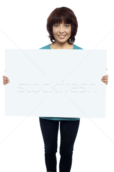 Woman holding billboard, your ad here Stock photo © stockyimages