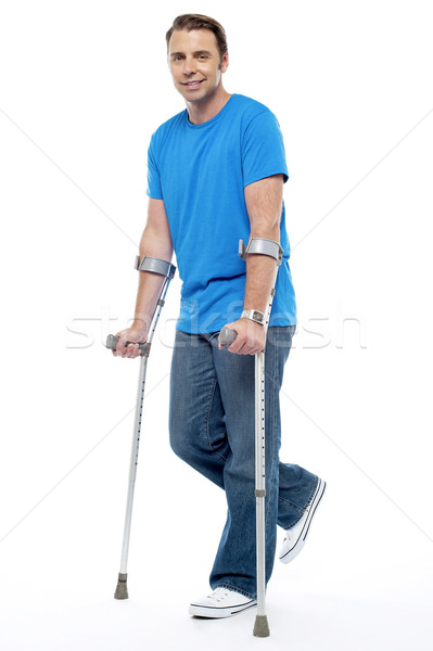Stock photo: Young man with crutches trying to walk