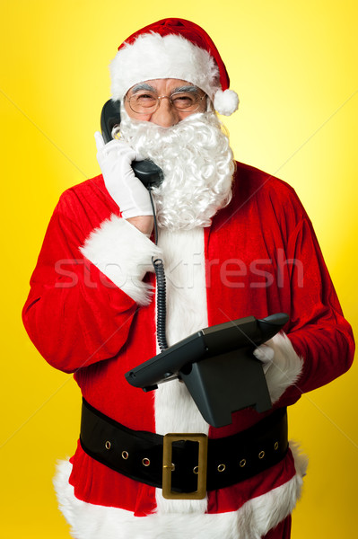 Smiling aged Santa attending phone call Stock photo © stockyimages