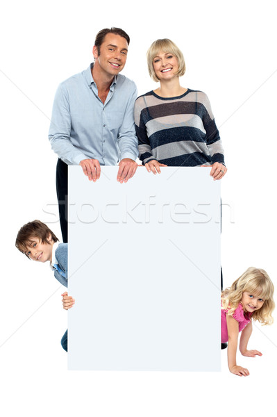 Lively family of four all around blank whiteboard Stock photo © stockyimages