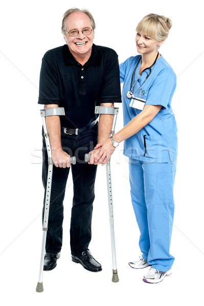 Experienced physician assisting her patient in recovery process Stock photo © stockyimages