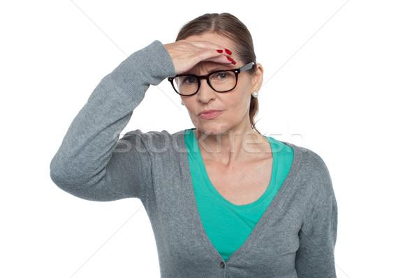 Kifejezéstelen nő néz távolság tárgy izolált Stock fotó © stockyimages