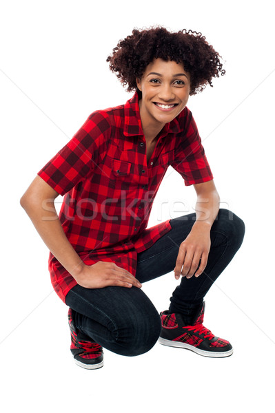 Smiling female model in squatting posture Stock photo © stockyimages