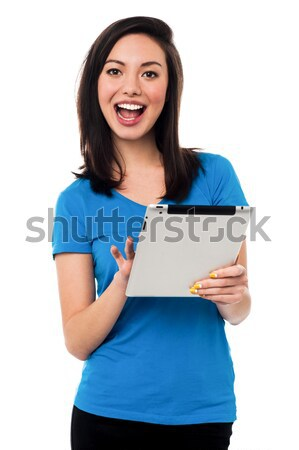 Attractive asian girl browsing on tablet device Stock photo © stockyimages
