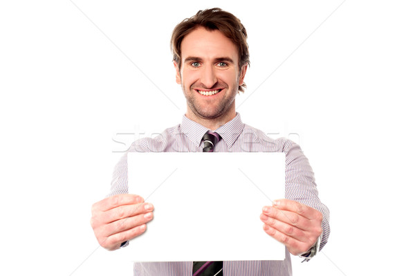 Male executive holding out blank ad board Stock photo © stockyimages