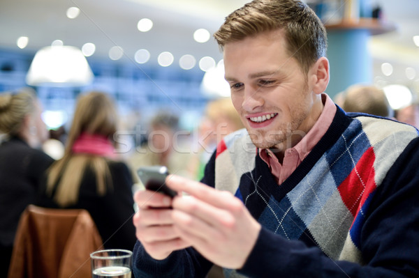 Young man in cafe and using his mobile phone Stock photo © stockyimages