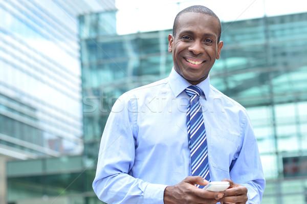 üzletember mobiltelefon boldog férfi igazgató pózol Stock fotó © stockyimages