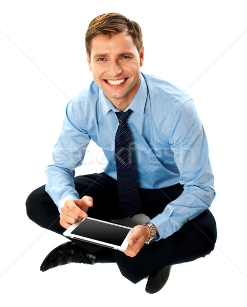 Man sitting on floor using touch screen device Stock photo © stockyimages