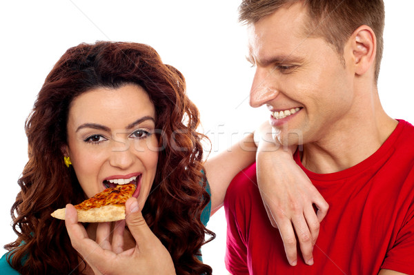 Girl enjoying pizza piece shared by her boyfriend Stock photo © stockyimages