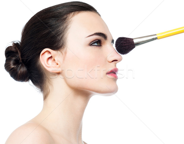 Pretty girl getting makeup applied on her face Stock photo © stockyimages