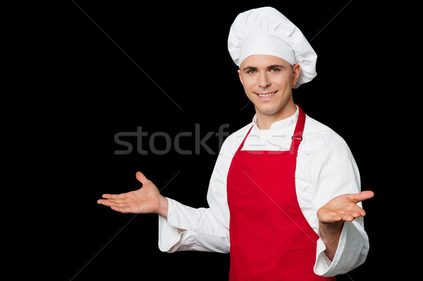 Young male chef welcoming his guests  Stock photo © stockyimages