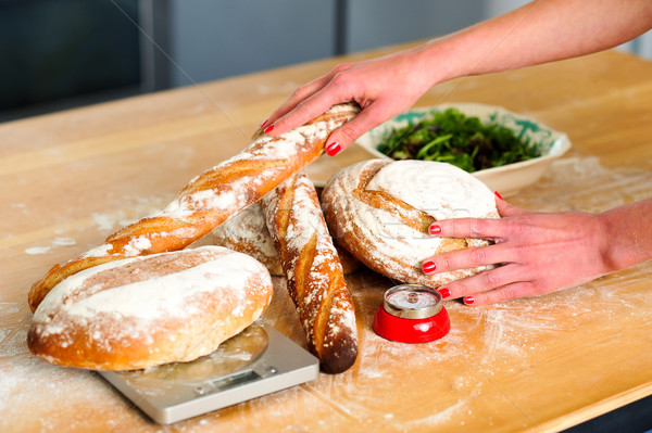 Females hands arranging baguettes and breads Stock photo © stockyimages