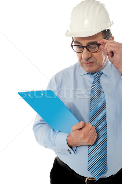 Experienced achitect in hardhat studying files. Isolated on white Stock photo © stockyimages