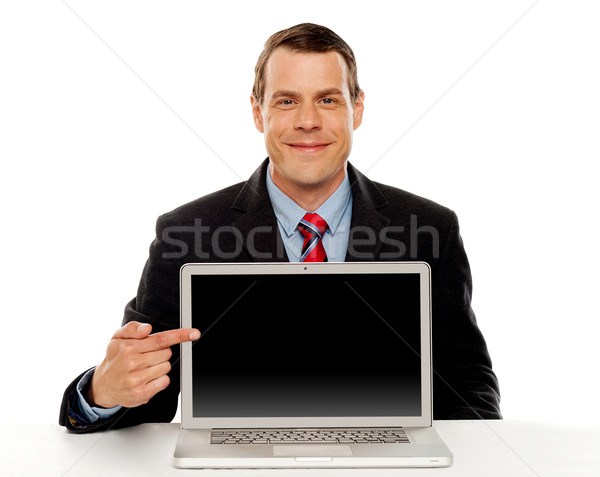 Businessman pointing at blank laptop screen Stock photo © stockyimages