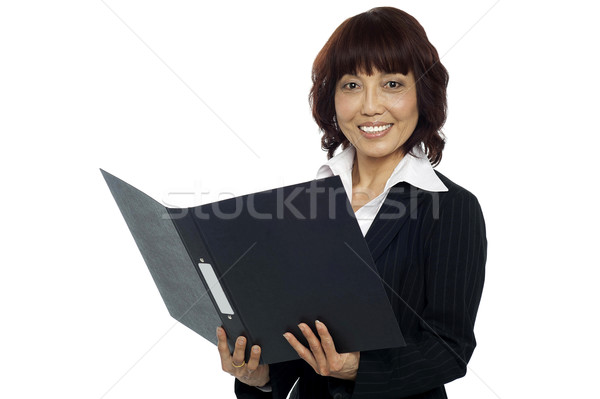 Young female asian boss going through the file Stock photo © stockyimages
