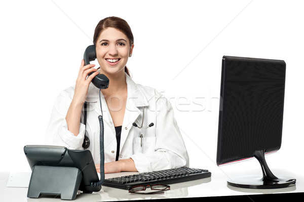 Female physician answering phone call Stock photo © stockyimages