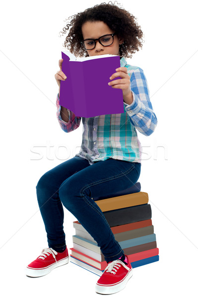 Young kid concentrating while reading a book Stock photo © stockyimages
