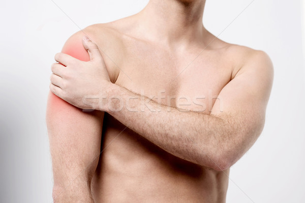 Muscular man discomfort on shoulder Stock photo © stockyimages
