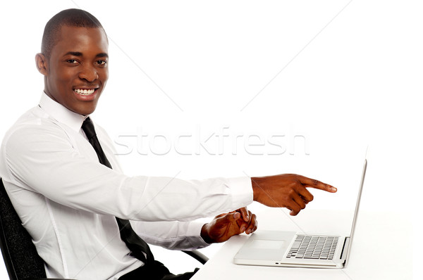 Smiling young african indicating on laptop screen Stock photo © stockyimages