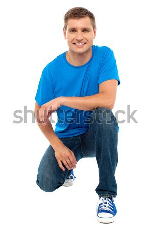Casual cool young guy semi seated on floor Stock photo © stockyimages