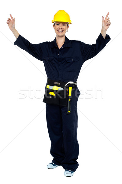 Smiling lady worker in jumpsuit raising her hands Stock photo © stockyimages