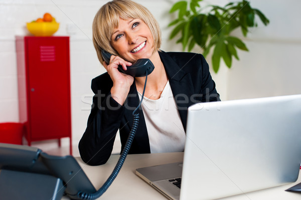 Cheerful lady engaged in a jovial conversation Stock photo © stockyimages