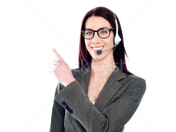 Female operator with headset pointing at something Stock photo © stockyimages