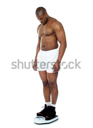 Athlete measuring his weight on weighing machine Stock photo © stockyimages