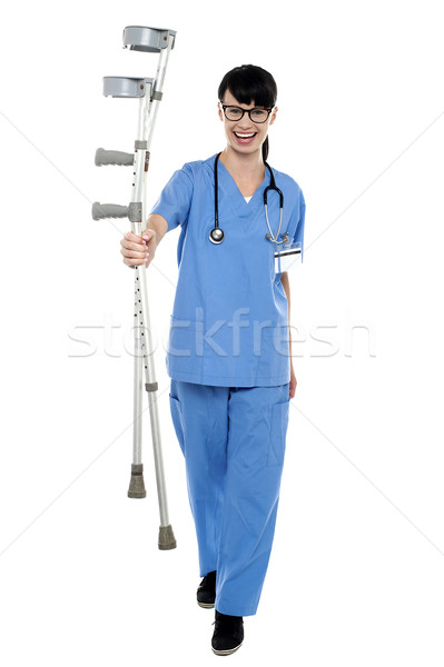 Orthopedic doctor walking towards camera with crutches in hand Stock photo © stockyimages
