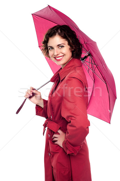 Glamorous woman standing under pink umbrella Stock photo © stockyimages