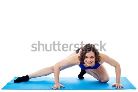 Fitt nő guggol kék stúdiófelvétel mosolyog Stock fotó © stockyimages