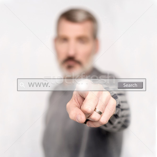 Man pointing at search bar on virtual screen Stock photo © stockyimages
