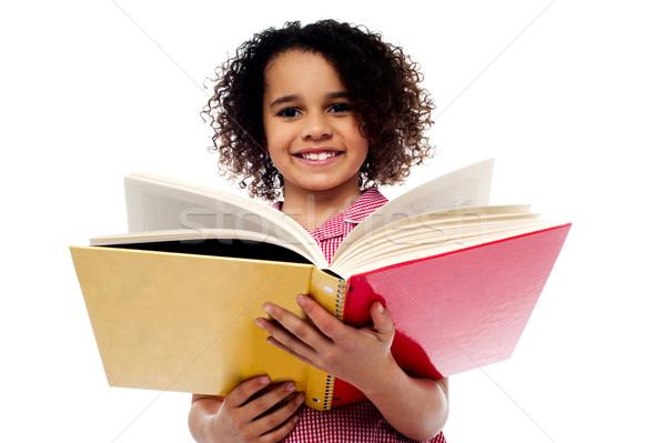 Imádnivaló iskolás lány olvas könyv mosoly mosolyog Stock fotó © stockyimages