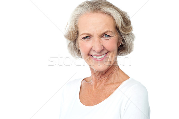 Happy smiling aged lady facing camera Stock photo © stockyimages