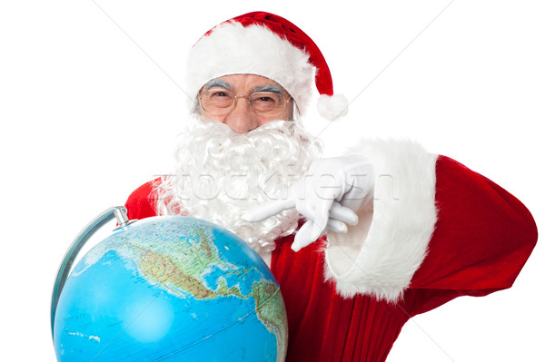 Expressionistic Santa pointing at north pole on globe Stock photo © stockyimages