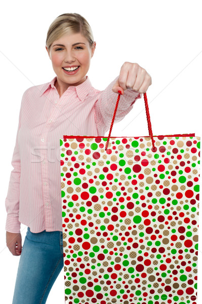 Cheerful blonde girl holding shopping bag in outstretched arm Stock photo © stockyimages