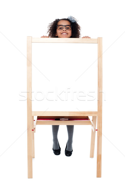 Girl peeping from behind white blank board Stock photo © stockyimages