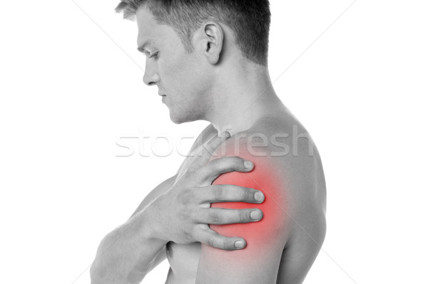 Guy holding his shoulder in pain Stock photo © stockyimages