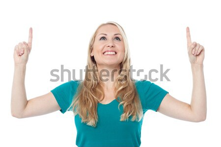 Casual woman looking and pointing upwards Stock photo © stockyimages