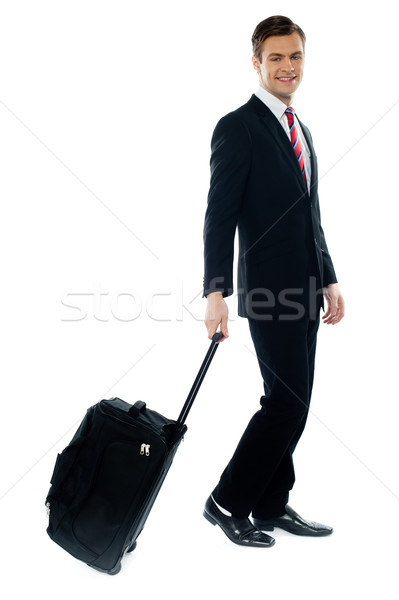 Handsome businessman dragging trolley bag Stock photo © stockyimages