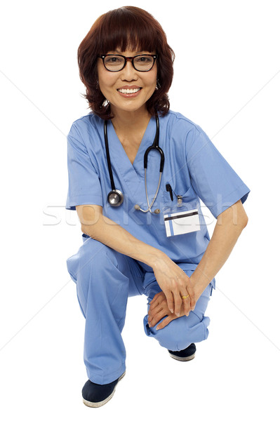 Female surgeon semi seated on floor. Studio shot Stock photo © stockyimages