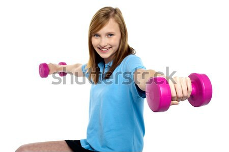Cute young girl stretching dumbbells sideways Stock photo © stockyimages