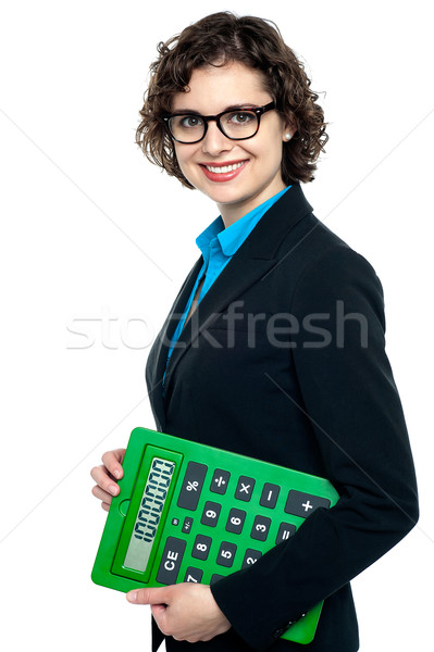 Side pose of a business lady holding calculator Stock photo © stockyimages