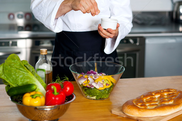 Chef sprinkling salt on vegetables Stock photo © stockyimages