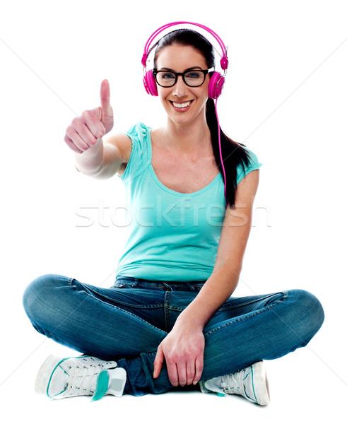 Thumbs-up woman enjoying music Stock photo © stockyimages