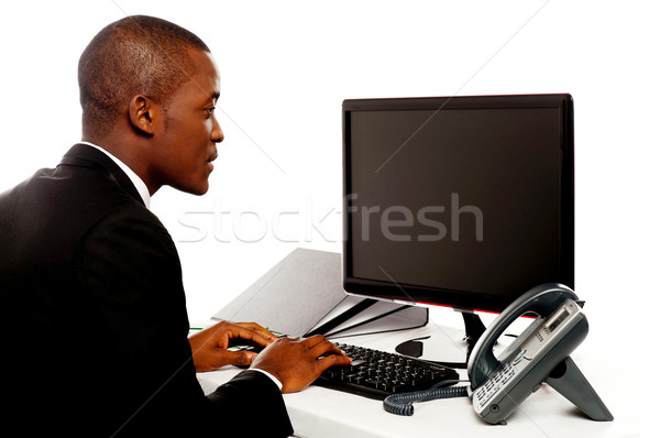 Male executive typing and looking at lcd screen Stock photo © stockyimages