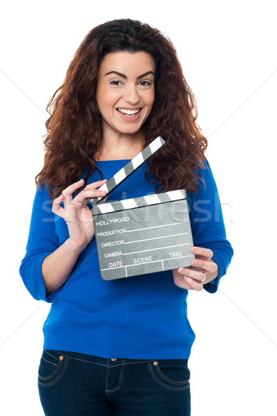 Cute woman in blue attire holding clapperboard Stock photo © stockyimages