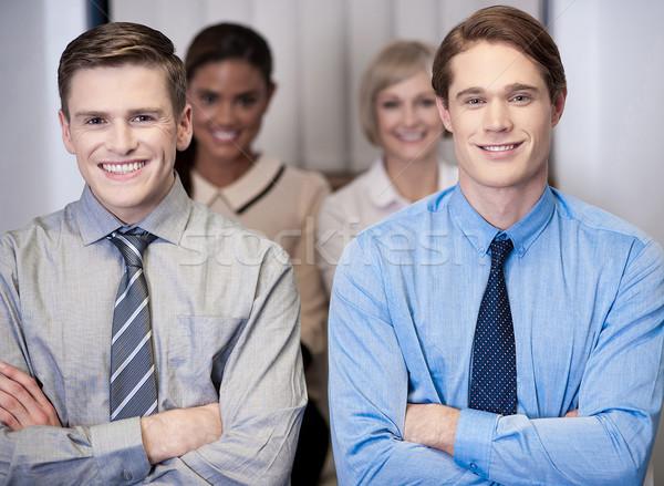 Stock photo: Cheerful work team posing, arms crossed.