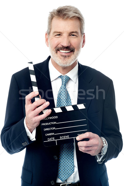 Smiling man showing a clapperboard to the camera Stock photo © stockyimages