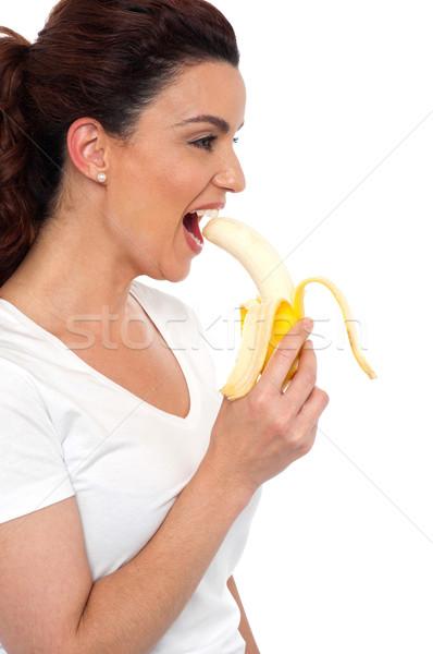 Photo stock: Vue · de · côté · brunette · femmes · manger · banane · isolé